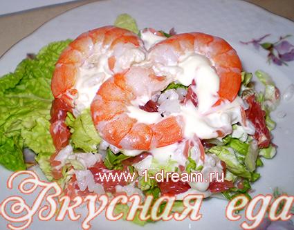 Вкусный салат с креветками на тарелке